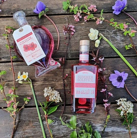 pink gin in a heart shaped bottle and pink Summer Solstice Gin with flowers from Heathercroft Meadow