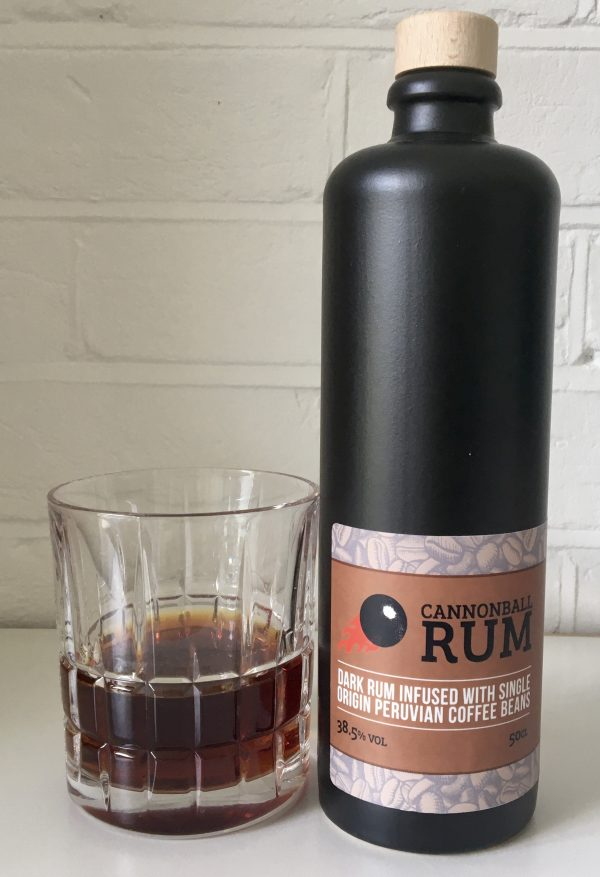 50cl black ceramic bottle of Cannonball Rum with dark rum in a glass